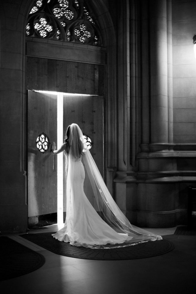 Black-and-White-wedding-photo-of-bride-walking-through-Duke-Chapel-Doors-Morgan-Henderson-